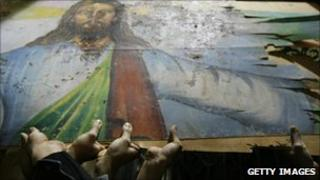 Egyptian Christians hold a blood-stained portrait of Jesus - January 2