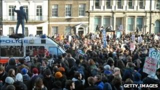 Demonstrators attack a Police van during a protest over university fees, on Whitehall in central London