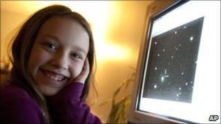 Kathryn Gray, 10, at home in Birdton, New Brunswick, Canada, on 3 Jan 2010, sits next to the computer monitor on which is the image in which she discovered the supernova