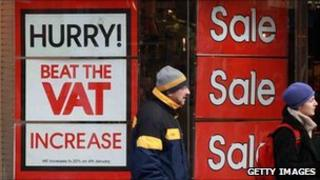 Shoppers pass a sign urging them to hurry and beat the VAT increase