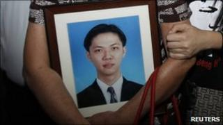 Teoh Beng Hock's mother holds his picture as they leave the courtroom in Shah Alam outside Kuala Lumpur