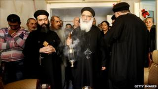 Relatives of Egyptian Copt Fawzi Bakhit who was killed in the New Year's Day church bombing in Alexandria gather behind a priest blessing Mr Bakhit's home with incense, 3 January 2011
