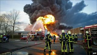 Dutch firefighters stand near the site of the blaze in Moerdijk, 5 January