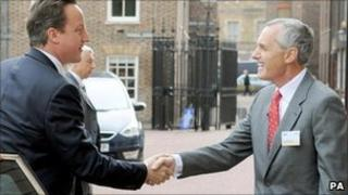 Prime Minister David Cameron shakes hands with Sir Andrew Cahn