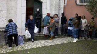 People waiting to collect donated food from a church in suburb of Lisbon