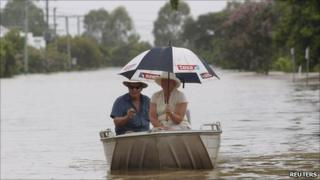 A couple make their way through Depot Hill, Rockhampton, as rain falls on 6 Jan 2010