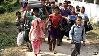 Indian villagers try to move to safer places following ethnic clashes at Salpara in Meghalaya on 6 January 2011