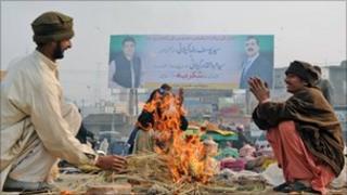 Vendors gather around a fire in Multan on 6 January 2010 - in the background, a billboard showing Pakistan's PM and his son