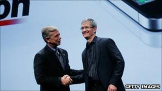 Verizon President and COO Lowell McAdam (left) shaking hand with Apple Chief Operating Officer Tim Cook