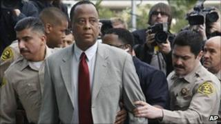 Conrad Murray accompanied by police officers