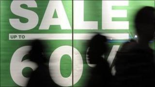People walking past sale sign