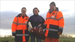 Rescuers with the injured swan
