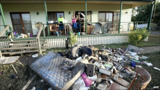 The Williams family throw damaged belongings outside their home at Fernvale, near Ipswich, southwest of Brisbane, Queensland