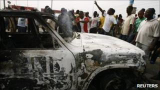 Students protest by a burnt UN vehicle in Abidjan (13 Jan)