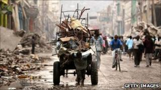 A child pulling rubble on a cart in Haiti