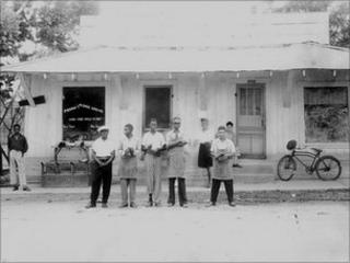 Frank Morris (fourth from left) in front of his shoe shop in Ferriday, Louisiana during the 1950s. [Image courtesy of Concordia Sentinel and William Brown, 2010]