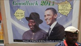 A Nigerian security man sits under a campaign poster of Nigeria President Goodluck Jonathan with US President Barack Obama, in Abuja, Nigeria, Wednesday 12 January 2011