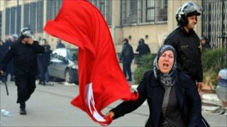 A Tunisian woman waves the national flag in front of the interior ministry during clashes between demonstrators and security forces in Tunis on January 14, 2011
