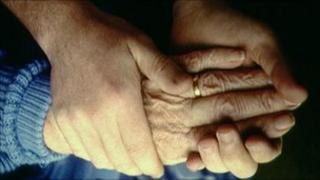 Elderly person and helper hold hands