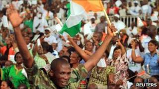 Supporters of Laurent Gbagbo wave their national flag during a rally in Abidjan on 15 January 2011