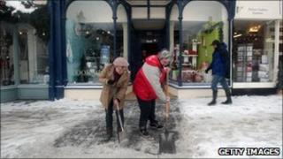 Shopkeepers clear snow from the street in Wells, Somerset (20 Dec 2010)
