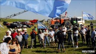 Protesting farm workers with tractors and Argentine flags gather beside a highway in the town of Oliva