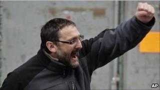 Txelui Moreno clenches his fist and shouts as police lead his son Iker away from his house, 18 January