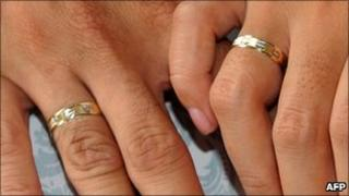 A couple holds hands showing their wedding rings during a wedding in Manila