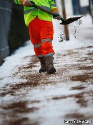 A council worker shovelling grit