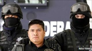 Suspected drug trafficker Flavio Mendez Santiago flanked by armed federal policemen at a news conference