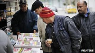 Men look at newspapers at a street kiosk in downtown Tunis, January 19, 2011