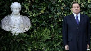Silvio Berlusconi poses beside a bust at Rome's Villa Madama, 18 January
