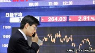 MAN IN FRONT OF STOCK MARKET DISPLAY