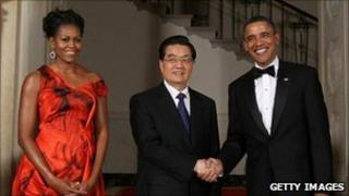 U.S. President Barack Obama (R) shakes hands with Chinese President Hu Jintao (C) as first lady Michelle Obama looks on