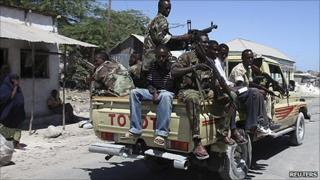 Somali government soldiers patrol along a street in Mogadishu, 2011