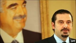 Lebanon's embattled caretaker Prime Minister Saad Hariri addresses Lebanese in front of a picture of his assassinated father Rafik Hariri