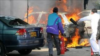 Karachi Electric Supply Company staff extinguish a burning car torched by sacked employees on 20 January 2011