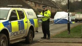 Police officer next to police car with forensic tent in the background