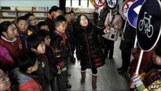 Chinese children holding traffic signs undergo a class on traffic security and manners, at a school in Dongyang in China's Zhejiang province, 20 January 2011