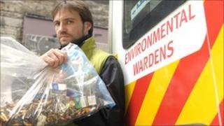 Environmental warden holding bag of cigarette butts
