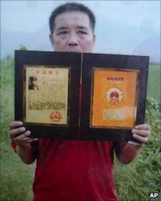 Photo released by Qian Yunhui's family of Mr Qian holding a copy of an award certificate presented by his villagers