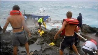 People clamber on the rocky shore on Christmas Island during a rescue attempt as a boat breaks up in the background