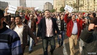 Crowd in Tahrir Square, Cairo carrying signs against President Mubarak.