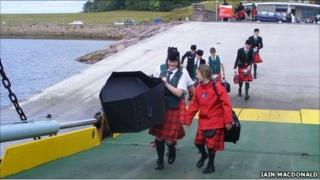 Members of a pipe band board the ferry after the opening ceremony. Image: Iain MacDonald/BBC