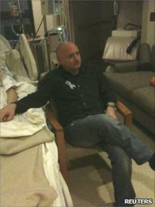 Mark Kelly watches Mr Obama's State of the Union address at Ms Giffords' bedside