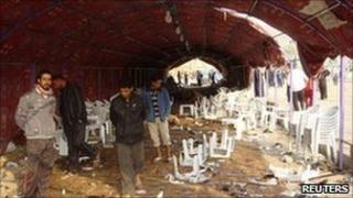 Residents inspect the site of a bomb attack inside a funeral tent in Baghdad. Photo: 27 January 2011