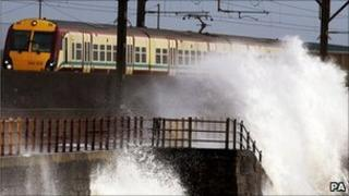 Train goes past sea front in Scotland (PA)