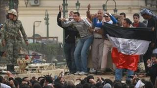 Protestors stand on army tanks in Tahrir Square