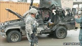 US troops and Afghan police inspect the wreckage of the deputy governor's car in Kandahar. Photo: 29 January 2011