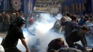 A policeman uses a baton against demonstrators fleeing in a cloud of tear gas in Alexandria. Photo: 28 January 2011